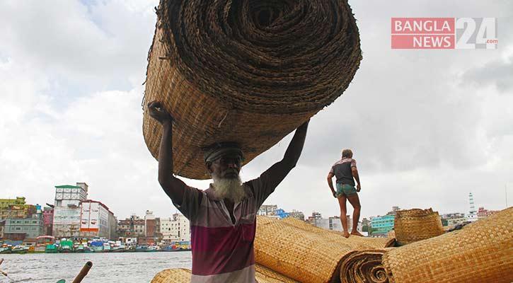 নৌকা থেকে নামানো হচ্ছে হোগলা পাতার পাটি/ছবি: ডিএইচ বাদল